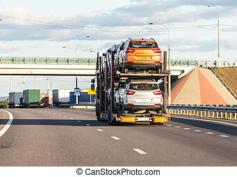 Car transporter carries cars along the highway, side view of...