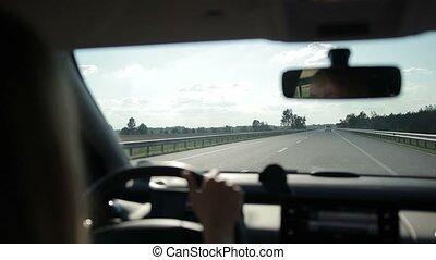Car traveling on asphalt highway on sunny day