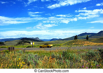 Yellow convertible travels the a highway through Lamar Valley in Yellowstone National Park.