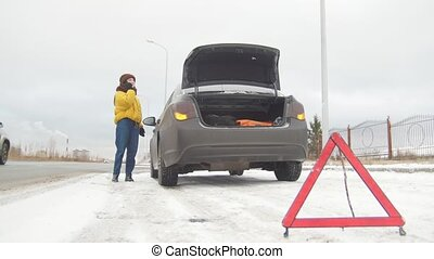Car Trouble. An emergency sign. Car trouble on a snowy country road. A young woman call the rescue service