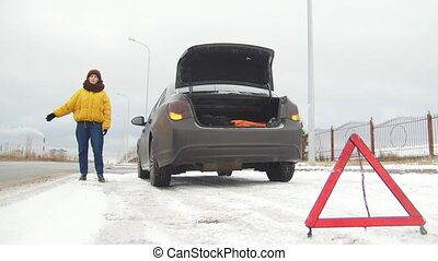 Car Trouble. An emergency sign. Car trouble on a snowy country road. A young woman tries to catch the car
