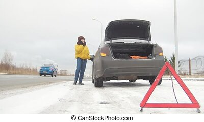 Car Trouble. An emergency sign. Car trouble on a snowy country road. Winter. A young woman call the rescue service