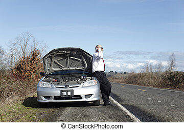 Businessman on cellphone with car trouble.