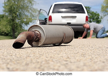 There is a muffler laying in the road in the foreground. In the background a man is looking under his van to see what happened.