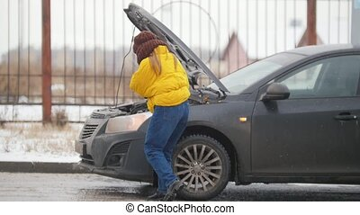 Car Trouble. Winter, cold weather. A young woman calls the rescue service and searching for help