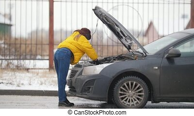 Car Trouble. Winter, cold weather. A young woman opens the hood, looking inside, rummaging in the engine, holding a phone