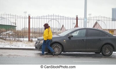 Car Trouble. Winter, cold weather. A young woman walks out of the car and opens the hood