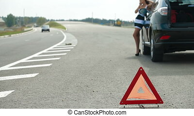 Car Troubles On The Road - Red warning triangle with a...