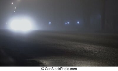car truck with switched on headlights driving on a road in...