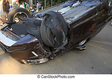 Car turned upside-down by accident on road