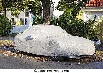 Car underneath a car cover