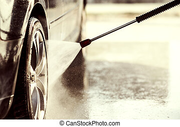 Cleaning the car with high pressure washer.