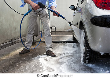 Car wash - Man, wahsing his car in the stall of a car wash,...