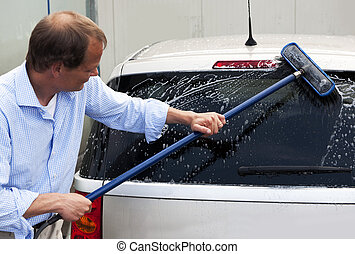 Car wash - Man washing the rear window of his car with a...