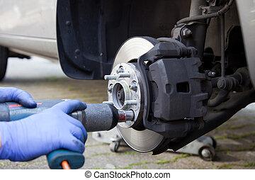 Car wheel changed by mechanic