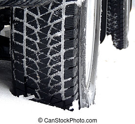 Car wheel with snow tire on the winter road