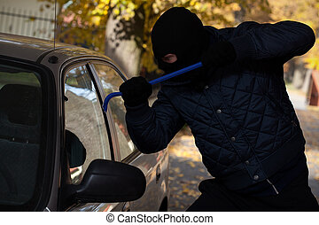Car window break-in - A man breaking in a car through its ...