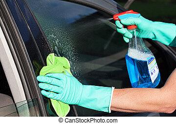 Car window washing - A man washing a car's window using a...