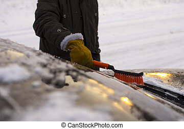 a man, cleans a car from snow