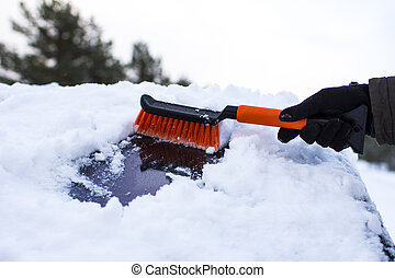 close-up of a man, cleans a car from snow