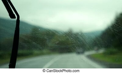 Car wipers removing heavy rain from the windshield during...