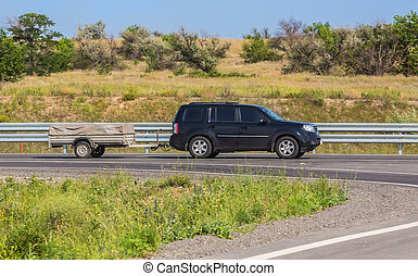 car with a trailer moves on country road