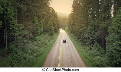 Car With Bicycles Passing On Rural Highway At Sunset