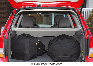 Red hatchback car loaded with open trunk and luggage