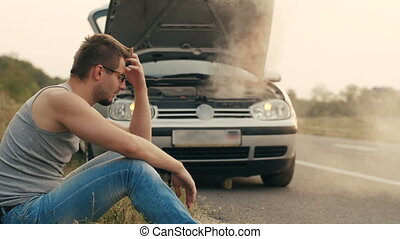 Car with overheated engine and sad man