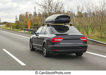 Car with roof luggage box container for travel on a road