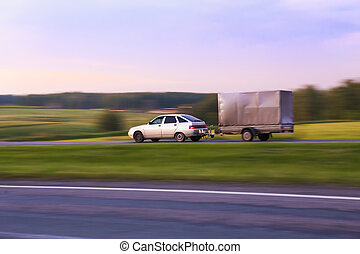 car with trailer moves on highway