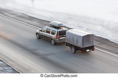 Car with trailer rides on the winter road - Car with a...