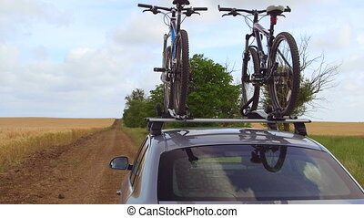 Car with two bicycles mounted on bike roof carrier on a country road