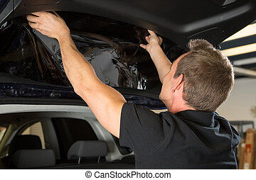 Car wrapper attaching tinting foil to car window - Car...