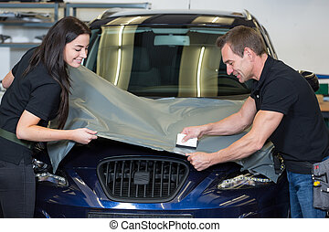 Car wrappers using squeegee to straighten vinyl film - Car...