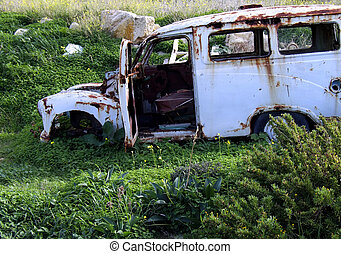 Old car left to rot as junk in a field