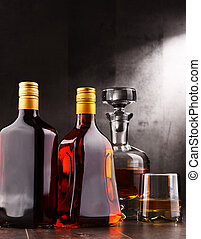 Carafe and bottles of assorted alcoholic beverages. -...