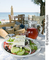 carafe of home made house rose wine and greek salad with...