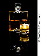 carafe of scotch whiskey or bourbon and drink with ice on black background