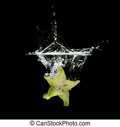 carambola splashing in water over black background