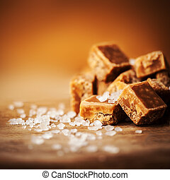 Caramel candies on brown background