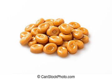 Caramel candies stack over white background. Closeup of circle shape candy group