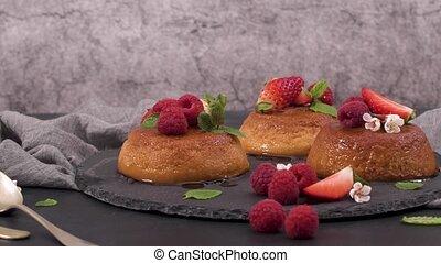 Caramel custard puddings on round slate on and dark kitchen countertop.