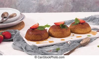 Caramel custard puddings on white ceramic tray and kitchen countertop.