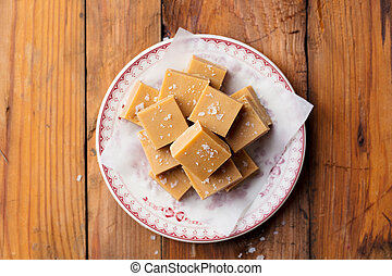 Caramel fudge candies on a plate. Wooden background. Top view.