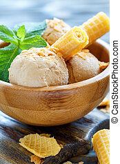 Caramel ice cream and wafer rolls in wooden bowl.