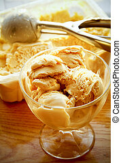 Caramel ice cream in glass on the table