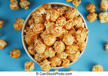Caramel popcorn in a cup on a blue background, top view.