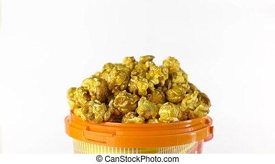Caramel popcorn rotates on a white background. Close up shot