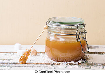 Jar of homemade caramel sauce, served with sugar cubes over wooden table